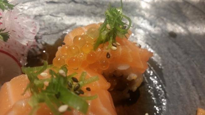 Uramaki ripieno di gamberoni in tempura, zenzero, nocciole, miso giapponese e pistacchi. Finitura con sashimi di salmone alla fiamma e verdure di stagione scottate